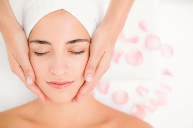 Mulher atraente que recebe massagem facial no centro de spa