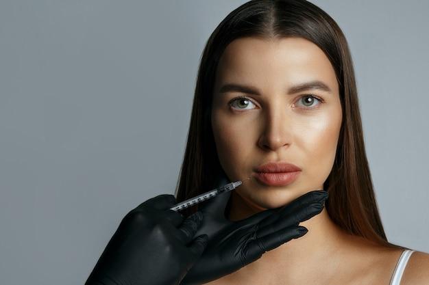 Mulher atraente recebendo injeção de ácido hialurônico nos lábios. foto do estúdio em um fundo cinza