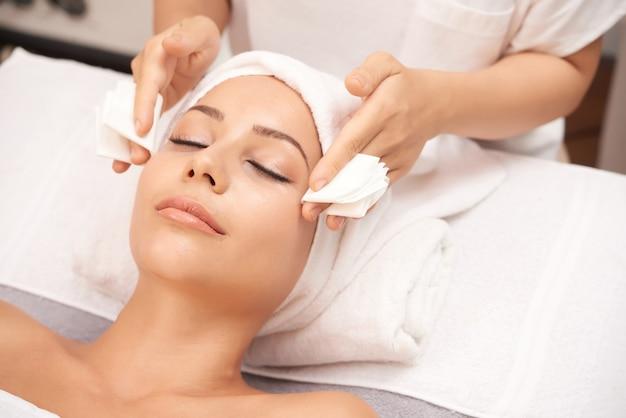 Mulher atraente, recebendo procedimentos de beleza de rosto no salão spa