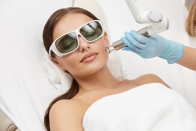 Mulher atraente recebendo tratamento facial na bochecha com laser em óculos, esteticista fazendo procedimentos faciais para mulheres em salão de spa