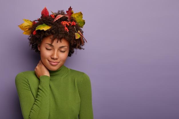 Mulher atraente relaxada com penteado afro, toca o pescoço, fica com os olhos fechados, tem olhar repousante, usa folhas no cabelo, roupas verdes
