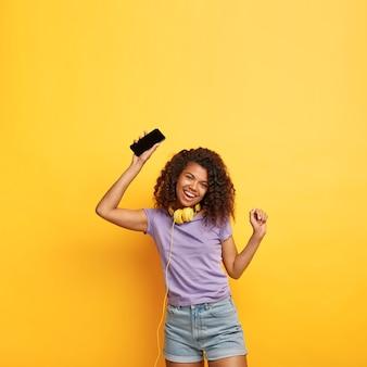 Mulher atraente relaxada e positiva com penteado afro, ouve música em fones de ouvido, canta junto com uma música, levanta os braços, desfruta de uma qualidade de som incrível