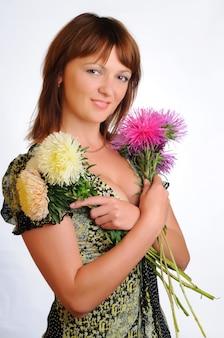 Mulher atraente ruiva caucasiana branca em vestido posando com buquê de flores. retrato isolado na parede branca