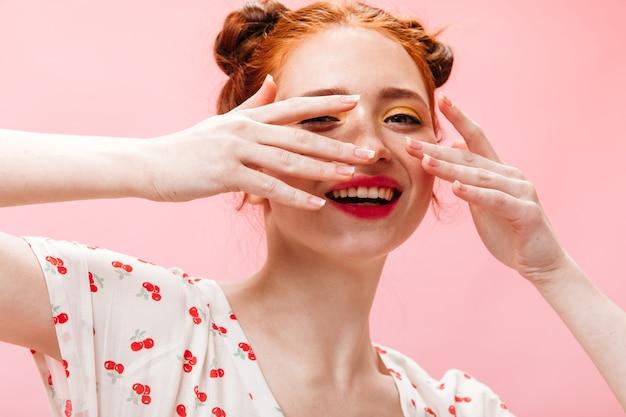 Mulher atraente ruiva cobre o rosto com as mãos. foto de mulher de olhos verdes com lábios rosados em fundo isolado.
