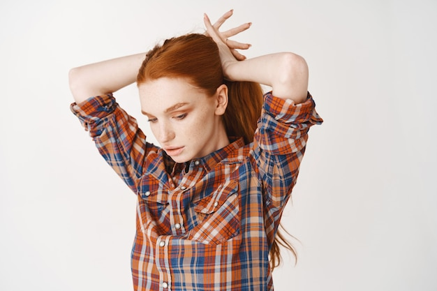 Mulher atraente ruiva com sardas amarrando o cabelo ruivo em um rabo de cavalo, encostada na parede branca