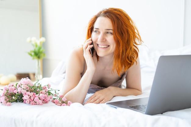 Mulher atraente ruiva de meia-idade de pijama deitada na cama usando telefone e laptop
