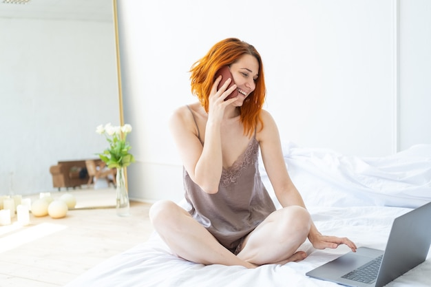 Mulher atraente ruiva de meia-idade de pijama, sentada na cama, usando telefone e laptop