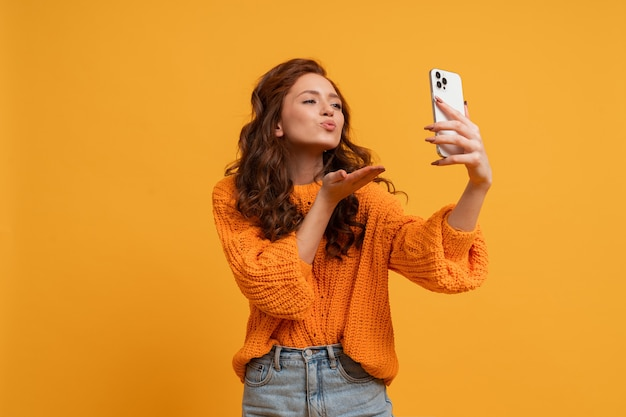 Mulher atraente ruiva em um casaco elegante de outono e jeans posando sobre a parede amarela