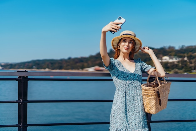 Mulher atraente ruiva posando em um dia ensolarado, fazendo selfie usando telefone, caminha ao longo do cais, perto da praia.