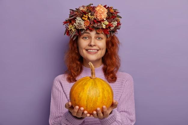 Mulher atraente ruiva usa coroa de flores outonal, segura uma abóbora madura e usa um suéter roxo.