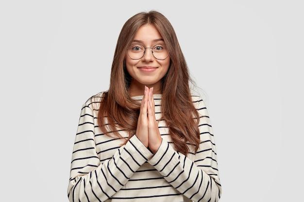Mulher atraente satisfeita com sorriso gentil, mantém as mãos rezando, vestida com roupas listradas