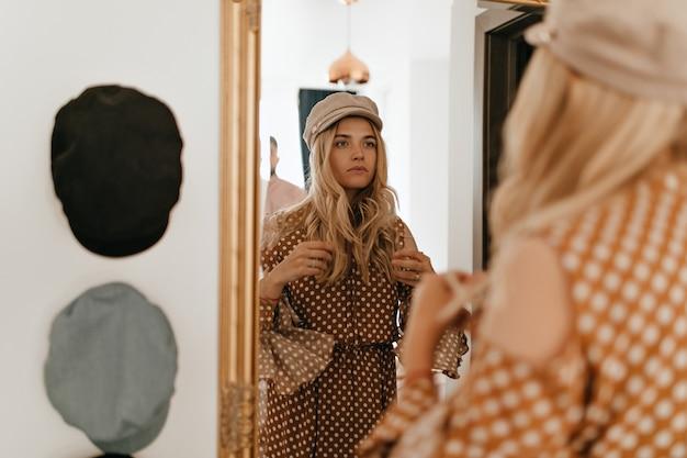 Mulher atraente se enfeita na frente do espelho com moldura dourada. mulher encaracolada em boné elegante posa em apartamento luminoso.