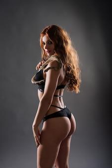 Mulher atraente sedutora e cobra python em estúdio