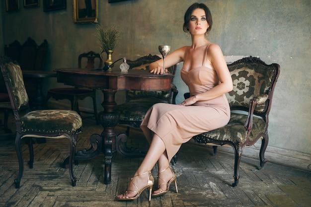 Mulher atraente, sedutora, sensual, elegante, vestido boho, sentada, café retrô vintage, bebendo vinho em taça, usando sapatos dourados de salto alto de luxo