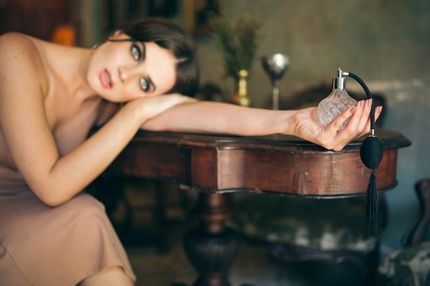 Mulher atraente, sedutora, sensual, elegante, vestido boho, sentada, café retrô vintage, segurando, perfume