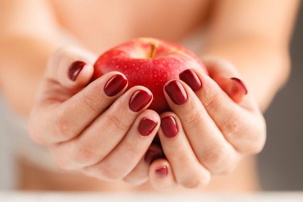 Mulher atraente, segurando a fruta comida maçã nas mãos bem cuidados