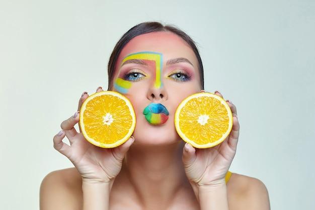 Mulher atraente segurando fatias de laranja na frente do rosto