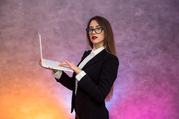 Mulher atraente segurando laptop branco. secretário, aluno ou professor posando em fundo abstrato