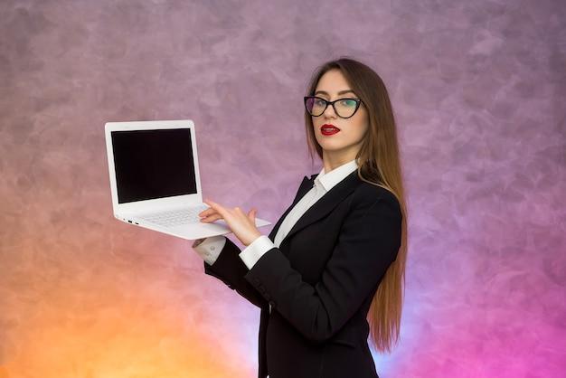 Mulher atraente segurando laptop de parede branca
