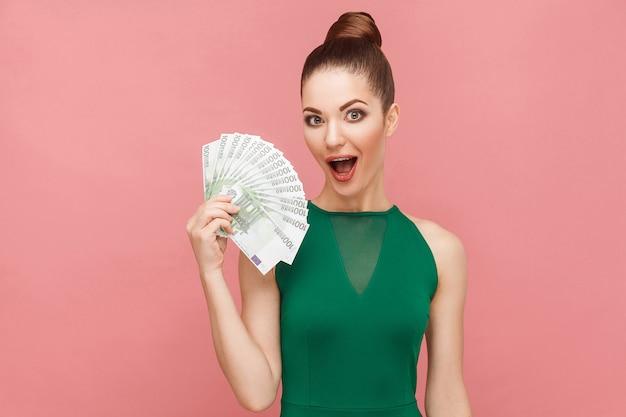 Mulher atraente segurando muitos euros e boca aberta