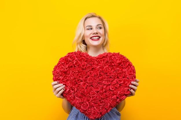 Mulher atraente, segurando o coração grande flor vermelha