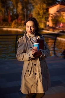Mulher atraente segurando um copo para viagem com uma bebida quente e um livro olhando para o lado enquanto caminhava no parque de outono contra o fundo de um lindo lago com folhas amarelas douradas caindo