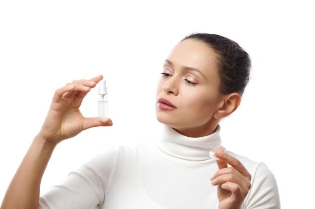 Mulher atraente segurando um frasco transparente com um produto de beleza ou farmacêutico ou um gel desinfetante