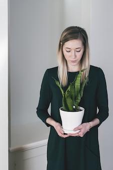 Mulher atraente, segurando um vaso de cerâmica branca com uma bela planta