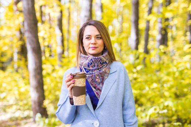 Mulher atraente segurando uma xícara de café para viagem na rua outono