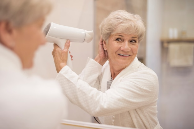 Mulher atraente sênior no banheiro