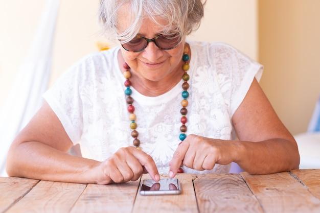 Mulher atraente sênior sentada e conversando com o telefone e sorrindo. cabelo grisalho e óculos de sol