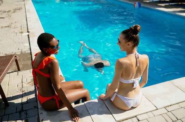 Mulher atraente sentada à beira da piscina