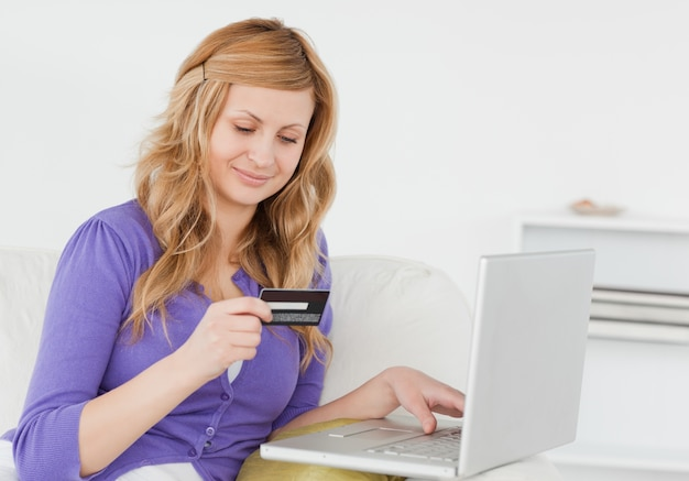 Mulher atraente sentada em um sofá vai fazer um pagamento na internet