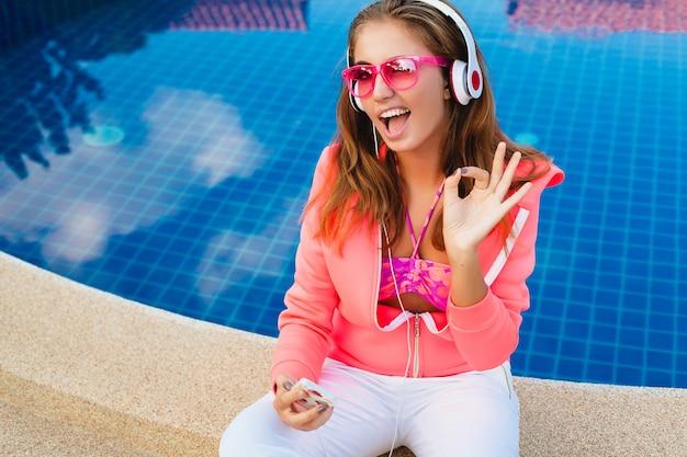 Mulher atraente sentada na piscina com capuz rosa colorido, óculos escuros, ouvindo música em fones de ouvido nas férias de verão, estilo esportivo, sinal de ok