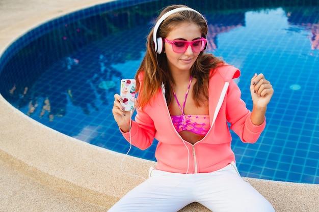 Mulher atraente sentada na piscina com um capuz rosa colorido usando óculos escuros e ouvindo música em fones de ouvido nas férias de verão, estilo esporte