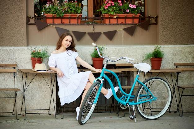 Mulher atraente, sentado do lado de fora na zona de café aconchegante com sua bicicleta azul vintage perto na frente do prédio decorado da cidade durante o dia quente de verão