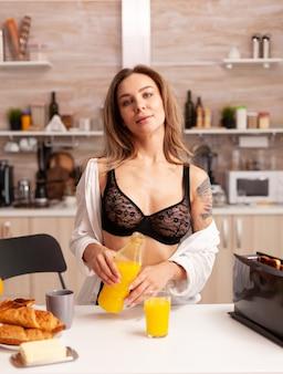Mulher atraente servindo suco fresco no copo no café da manhã na cozinha. jovem mulher sexy e sedutora com tatuagens bebendo suco de laranja caseiro e saudável, refrescante domingo de manhã