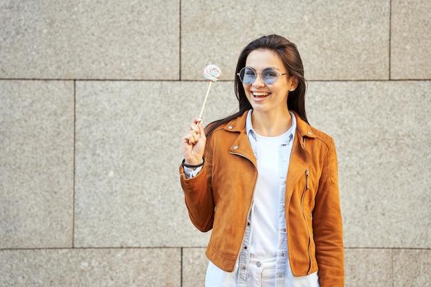 Mulher atraente sorridente de óculos de sol, posando para a câmera