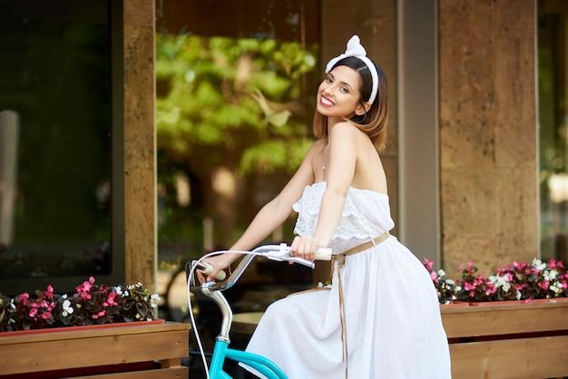 Mulher atraente sorridente, montando uma bicicleta azul, passando o café decorado com flores e painéis de madeira.