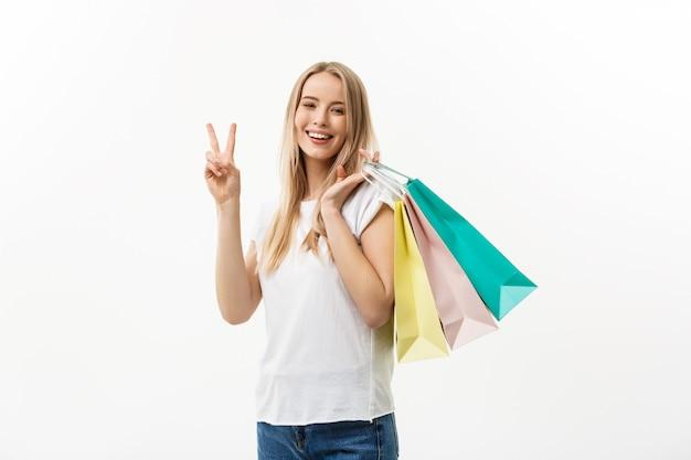 Mulher atraente sorridente segurando sacolas de compras, fazendo sinal de paz