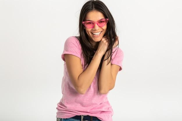 Mulher atraente sorrindo em camiseta rosa isolada usando óculos de sol rosa, cabelo longo morena