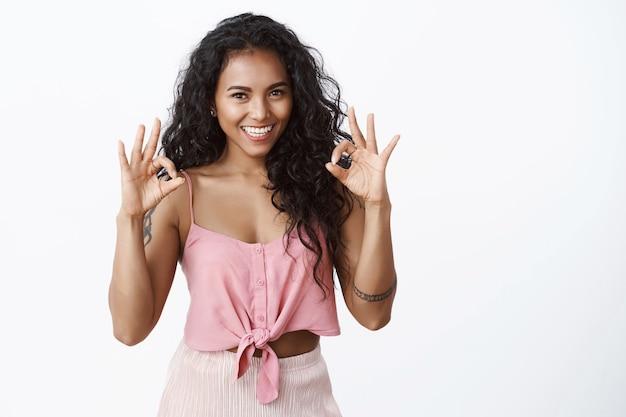 Mulher atraente sortuda e confiante com tatuagens, mostrando gesto de confirmação de ok, aprovando, aceitando e gostando do seu plano, sorrindo satisfeita, em pé na parede branca