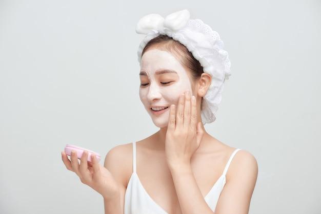 Mulher atraente spa aplicando máscara facial de argila isolada no fundo branco.