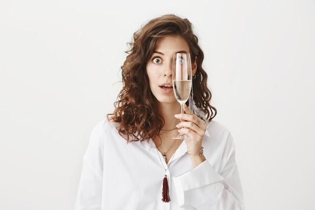 Mulher atraente surpreendida segurando uma taça de champanhe sobre o olho