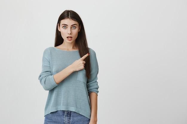 Mulher atraente surpresa sorrindo, apontando o canto superior direito no anúncio