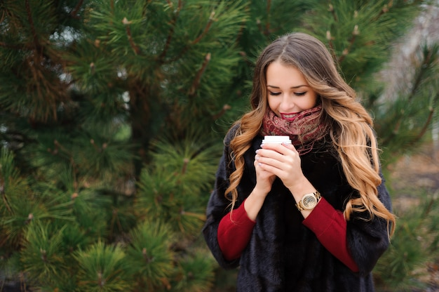 Mulher atraente tem um coffee break na rua no dia de outono