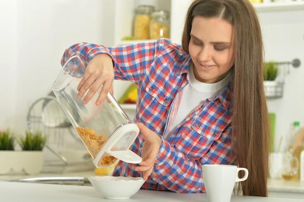 Mulher atraente tomando café da manhã no interior da cozinha
