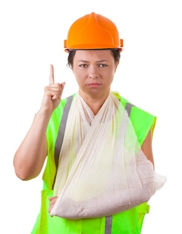 Mulher atraente, trabalhadora com jaqueta de segurança e capacete amarelo, com o braço ferido na tipóia em um fundo branco