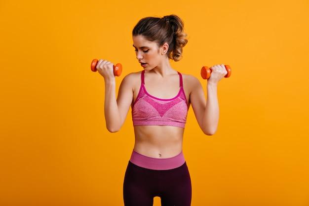 Mulher atraente treinando com halteres