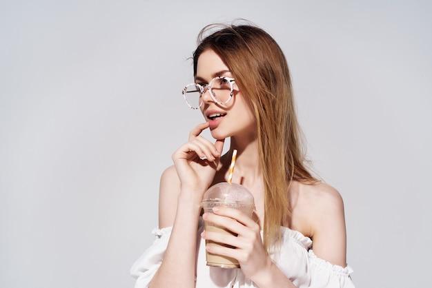 Mulher atraente, um copo com uma bebida na mão, vista recortada